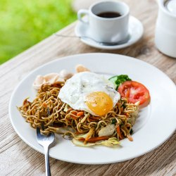 homemade indonesian fried noodle with a cup of hot tea